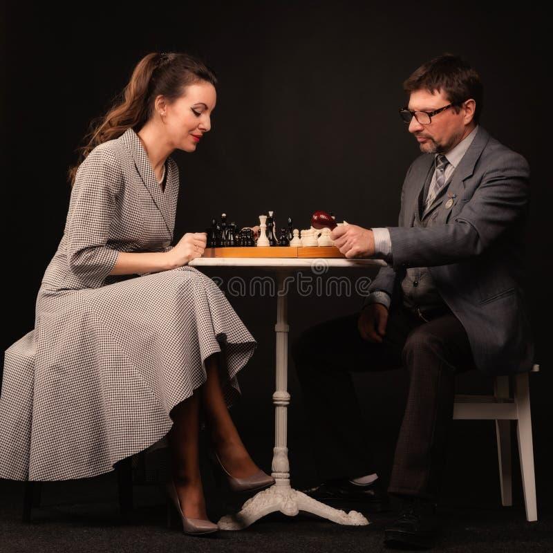 有女孩的一个人下棋并且抽在一黑暗的backgr的一个管子 库存照片