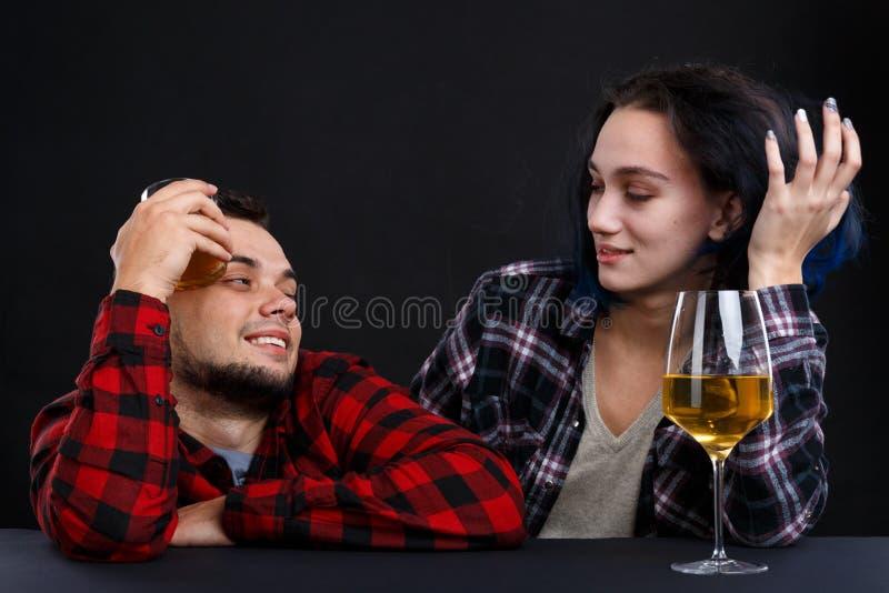 有女孩的一个人放松了与酒精在黑背景的一个酒吧柜台 免版税库存照片