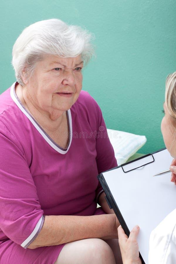 有女性医生和剪贴板的前辈 库存图片