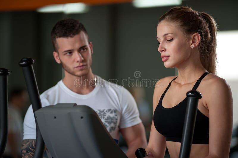 有女性客户的年轻男性教练健身房的 免版税图库摄影