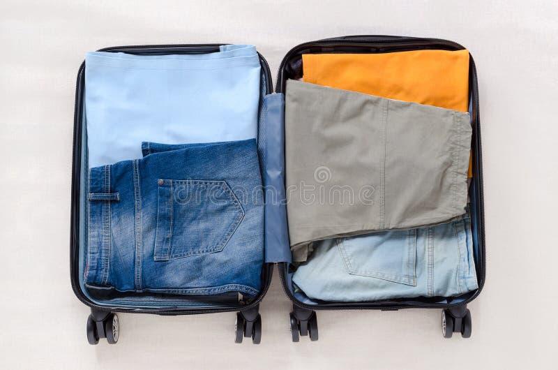 有女性或男性衣裳的开放旅行手提箱旅行的,顶视图 免版税库存图片