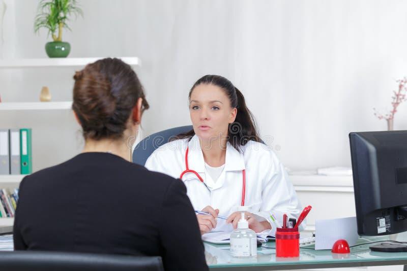 有女性的医生患者的正面新闻 库存图片