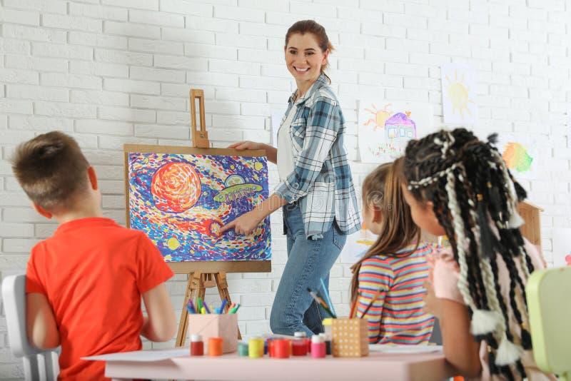 有女老师的孩子绘的教训的 库存照片