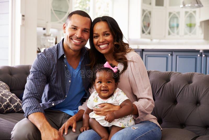 有女婴的愉快的父母坐mumï ¿ ½ s膝盖 库存照片