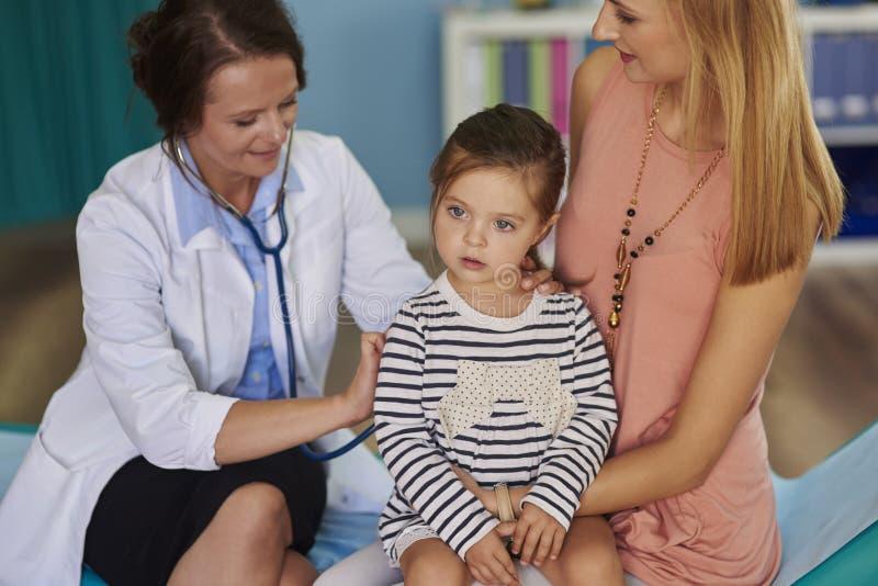 有女婴的母亲在医生的办公室 免版税库存图片