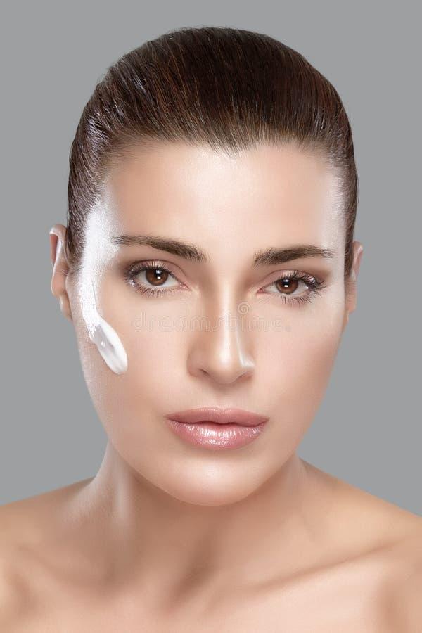有奶油的温泉女孩在她的面孔。Skincare概念 图库摄影