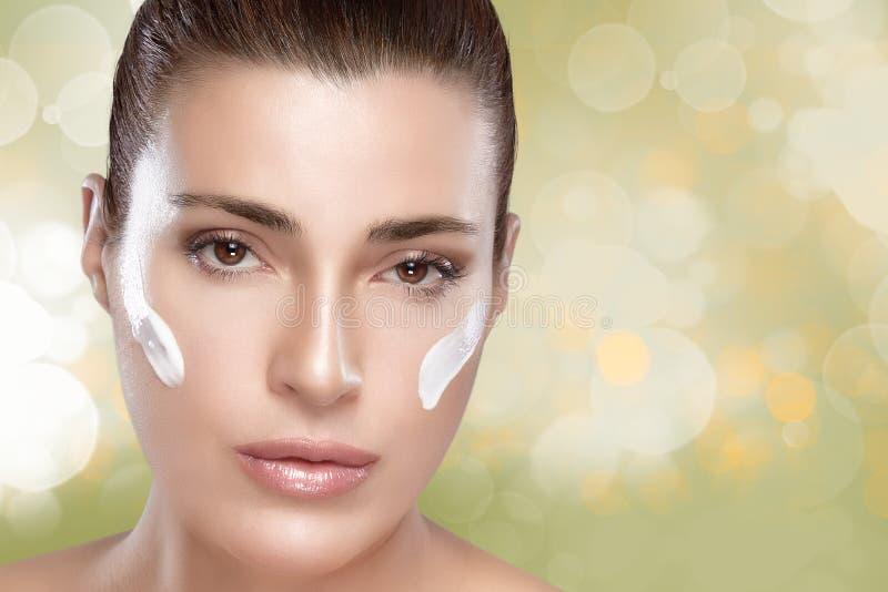 有奶油的温泉女孩在她的面孔。Skincare概念 库存照片