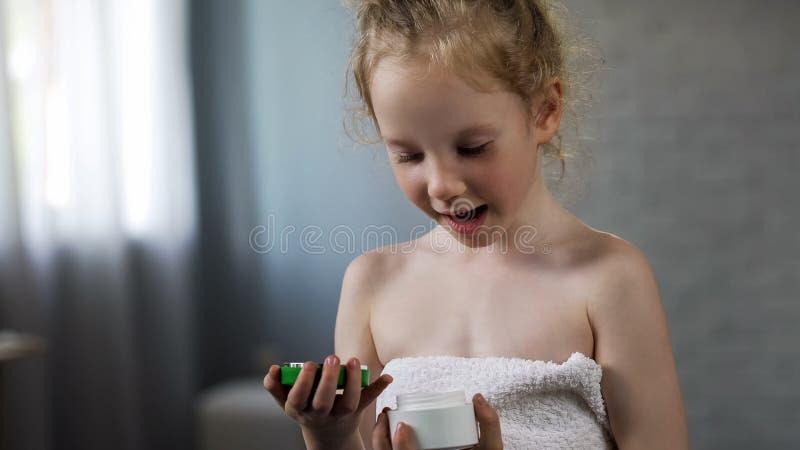 有奶油色管的微笑的白肤金发的女孩打开的母亲管,准备投入它  免版税库存照片