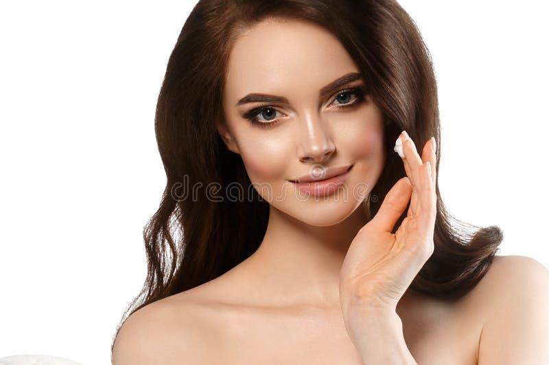 有奶油色面孔皮肤护理概念的,健康干净的新面孔皮肤关闭妇女,与creanm的女性模型在手中 免版税库存图片