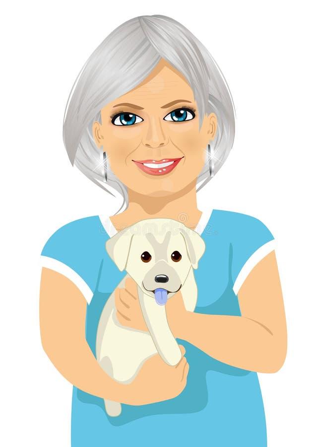 有她亲切的小的拉布拉多小狗的年长妇女 皇族释放例证