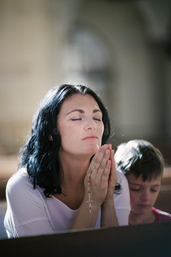 有她儿子祈祷的妇女 库存照片