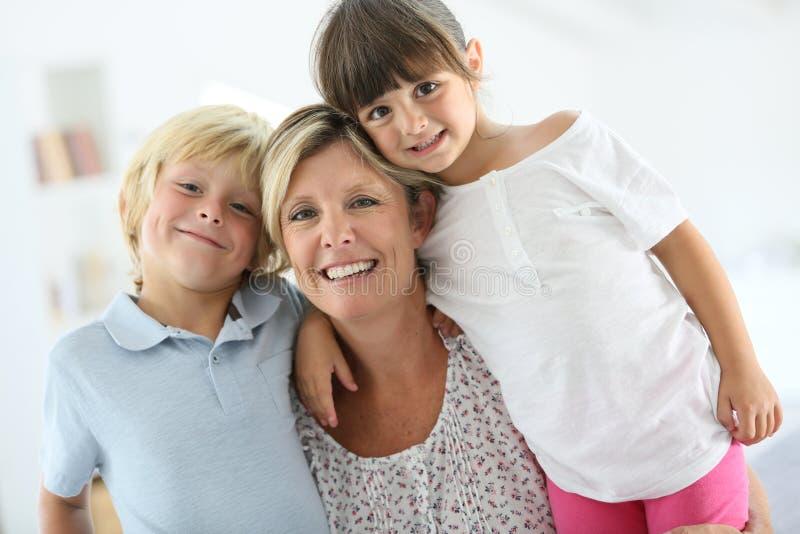 有她儿童微笑的愉快的母亲 图库摄影