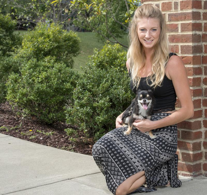 有她可爱的小狗的美丽的年轻白肤金发的妇女 库存照片