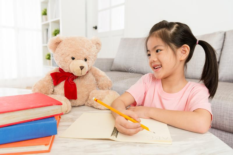 有她喜爱的玩具熊的女性孩子学生 免版税库存图片