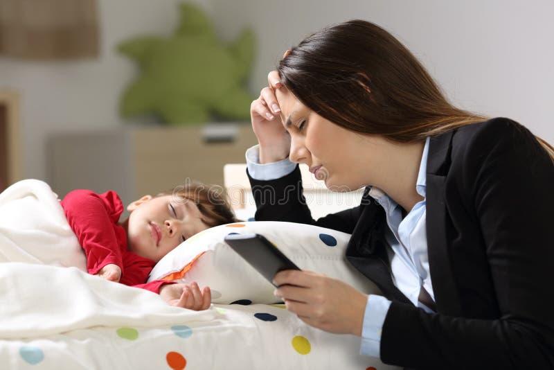 有她女儿睡觉的疲乏的工作者母亲 图库摄影
