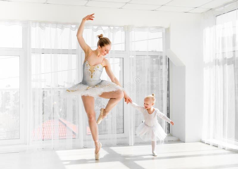 有她小的女儿跳舞的年轻华美的芭蕾舞女演员在演播室 图库摄影