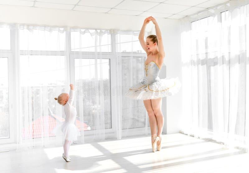 有她小的女儿跳舞的年轻华美的芭蕾舞女演员在演播室 免版税库存图片