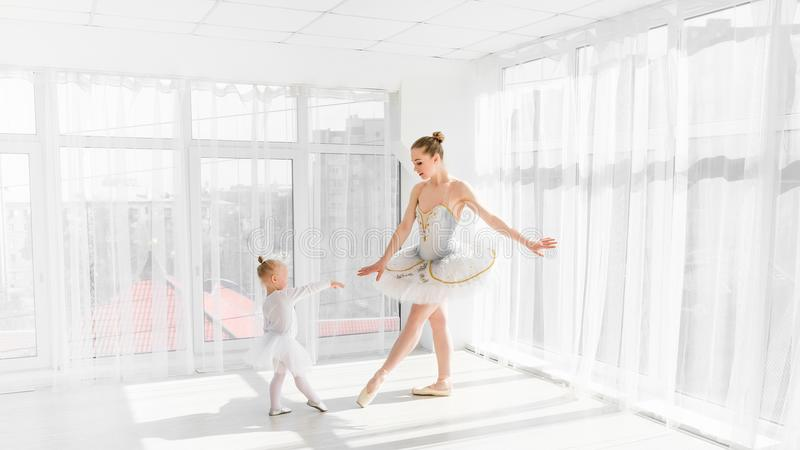 有她小的女儿跳舞的年轻华美的芭蕾舞女演员在演播室 免版税库存照片
