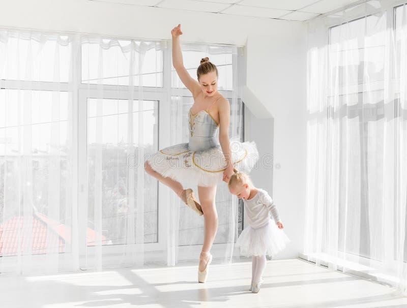 有她小的女儿跳舞的年轻华美的芭蕾舞女演员在演播室 库存照片