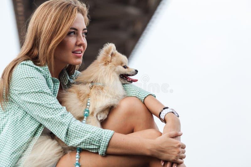 有她小的逗人喜爱的狗的美丽的女孩 免版税库存照片