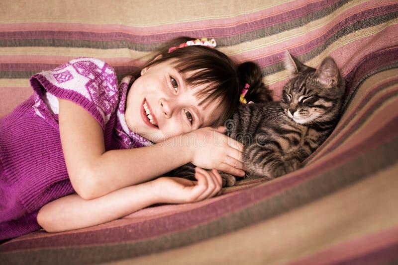 有她心爱的猫的逗人喜爱的小女孩 库存照片