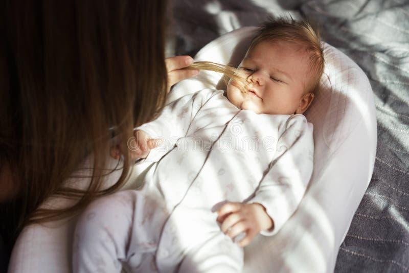 有她新出生的儿子的母亲在阳光的床上 库存图片