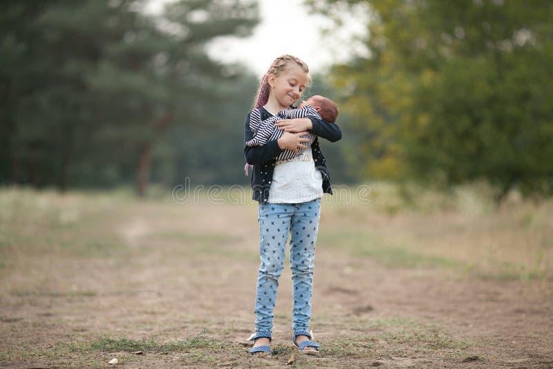 有她新出生的兄弟的儿童女孩步行的在公园 库存图片