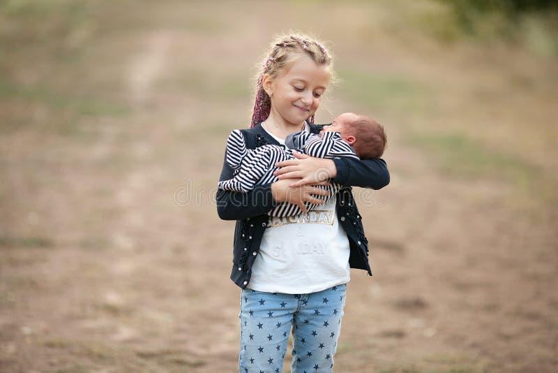 有她新出生的兄弟的儿童女孩步行的 关闭 免版税库存照片
