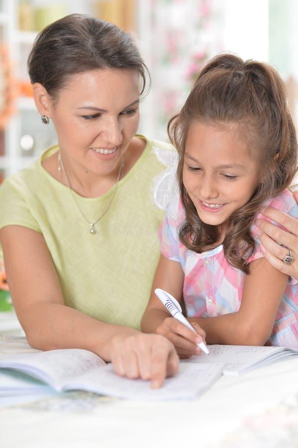 有她的一起做家庭作业的母亲的逗人喜爱的小女孩 免版税库存图片