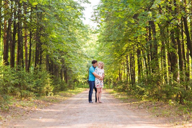有她的丈夫的愉快的年轻孕妇户外 图库摄影