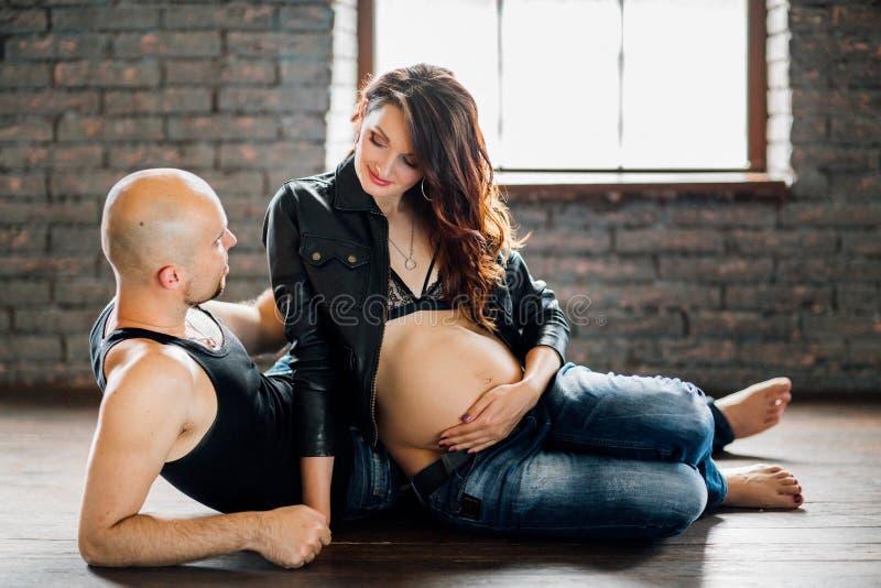 有她的丈夫的年轻人孕妇在演播室 免版税库存照片