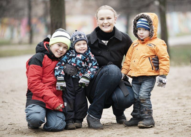 有她的三个幼儿的愉快的母亲 库存照片