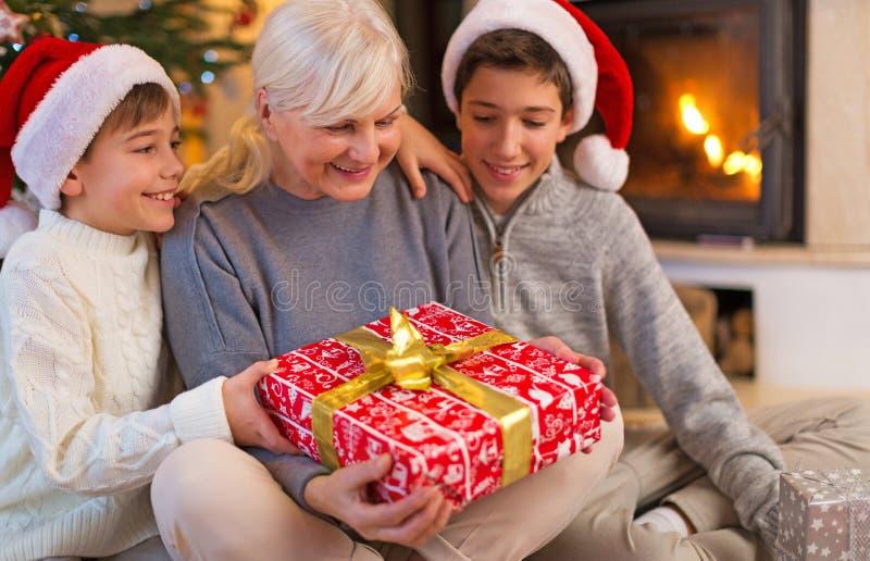 有她的两个孙的祖母,拿着圣诞节礼物 免版税图库摄影