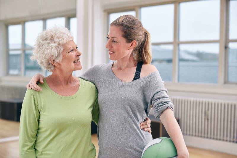 有她的个人教练员的愉快的资深妇女在健身房 免版税库存照片