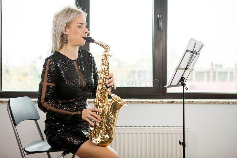 有她的乐器的萨克斯管吹奏者妇女在窗口 图库摄影