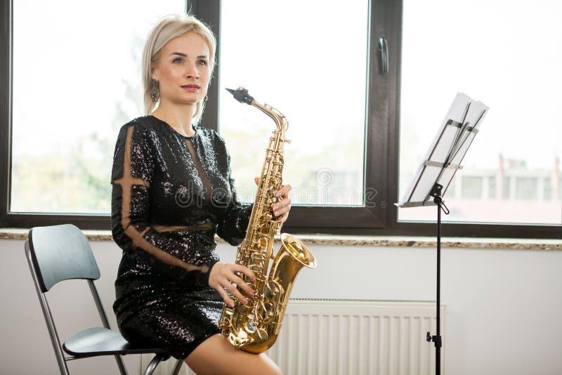 有她的乐器的萨克斯管吹奏者妇女在窗口 免版税库存图片