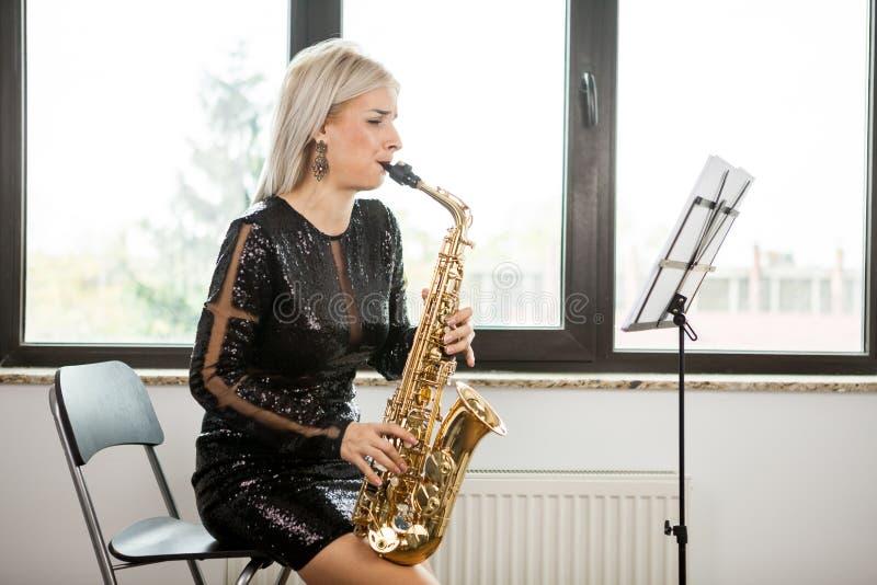 有她的乐器的萨克斯管吹奏者妇女在窗口 库存图片