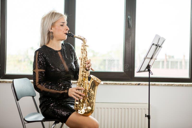 有她的乐器的萨克斯管吹奏者妇女在窗口 免版税图库摄影
