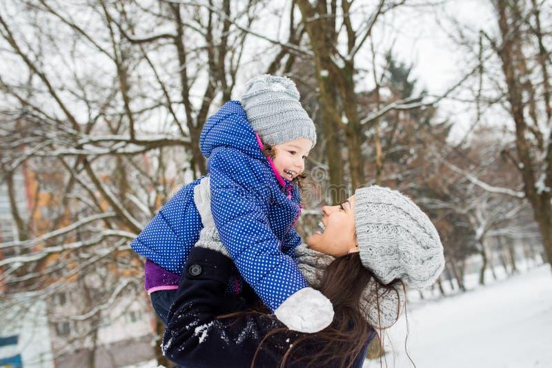 有她的使用外面在冬天自然的女儿的母亲 库存图片