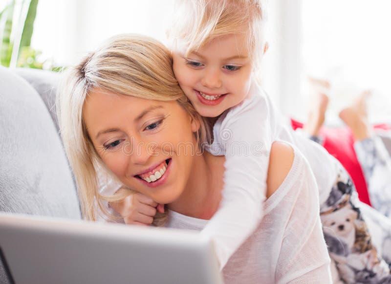 有她的使用片剂计算机的母亲的小女孩 库存照片