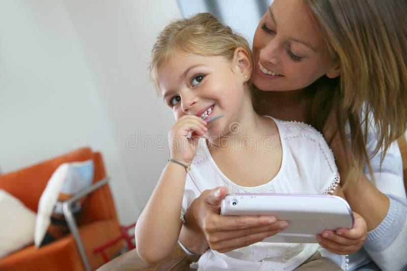 有她的使用电子游戏球员的小女孩的母亲 库存图片