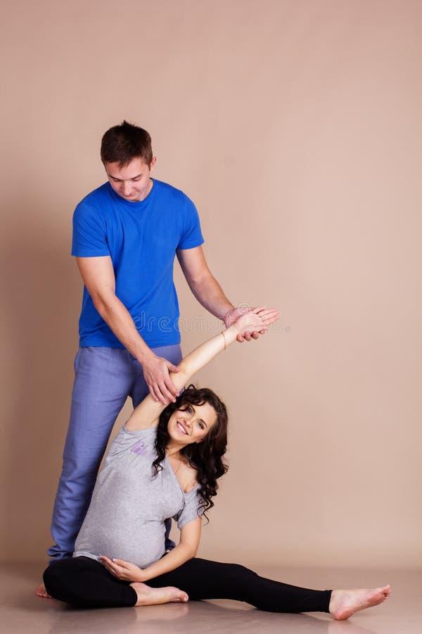 有她的做体育的男朋友的怀孕的女孩 免版税库存图片