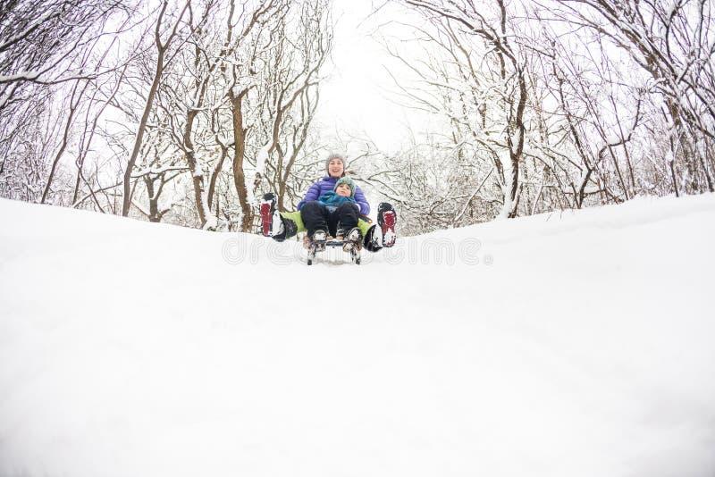 有她的儿子乘驾的一名妇女在雪橇的小山下 免版税图库摄影