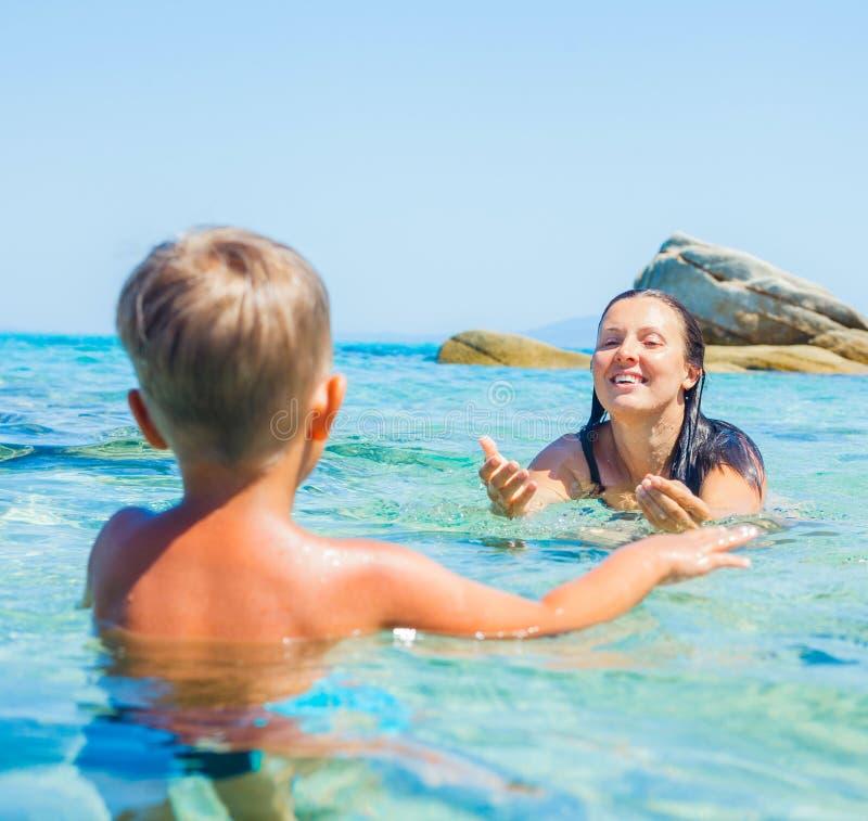有她的儿子游泳的母亲在海运 免版税图库摄影