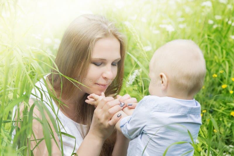 有她的儿子的愉快的母亲在草甸 免版税库存图片