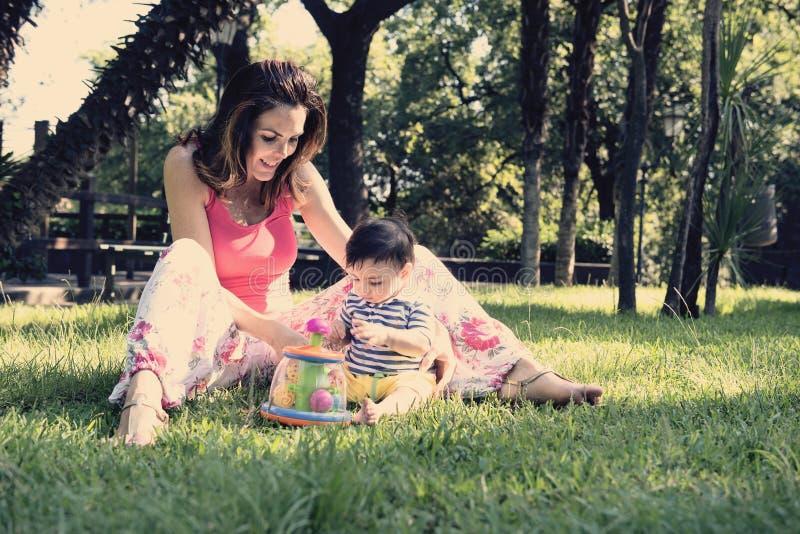 有她的儿子的母亲公园温暖的过滤器的申请了 免版税库存照片
