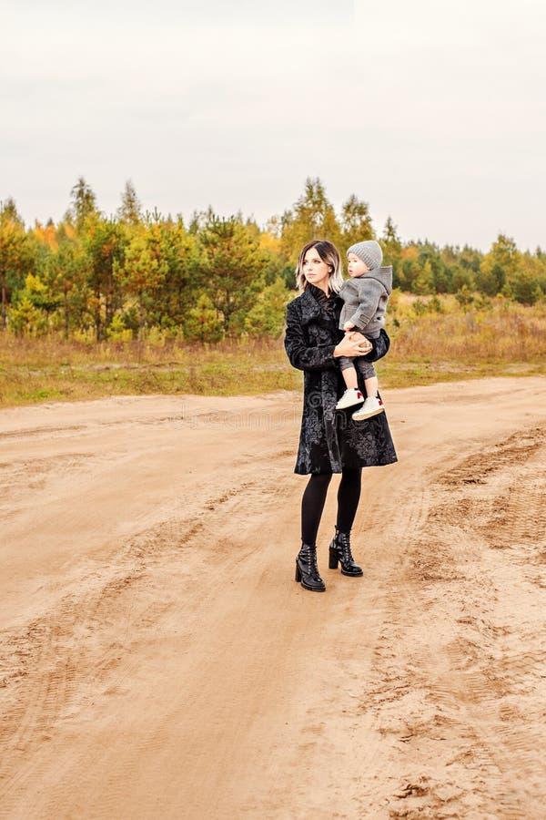 有她的儿子的母亲她的胳膊的沿着走多灰尘的含沙农村路 免版税库存照片