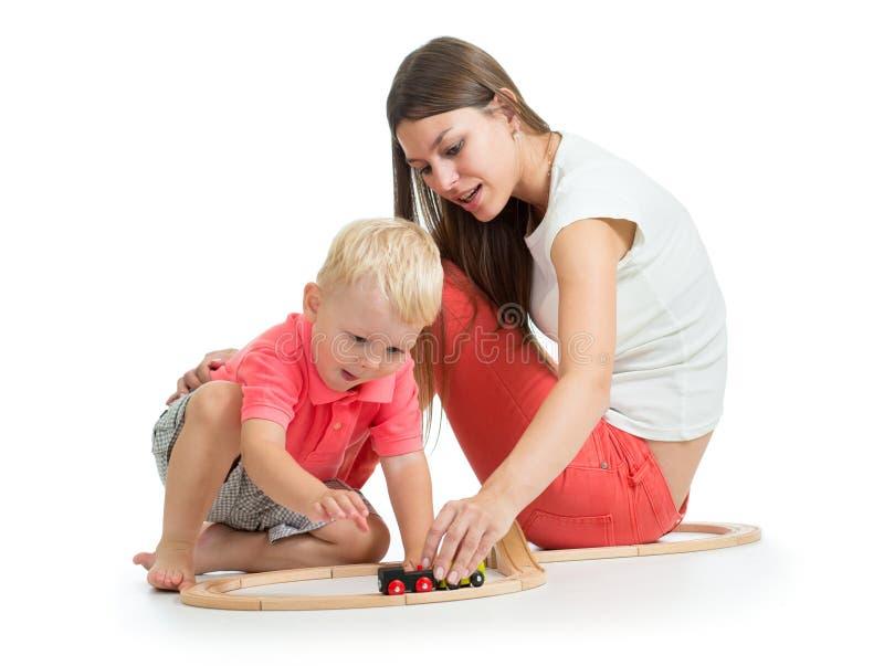 有她的儿童儿子的年轻母亲演奏铁路玩具 免版税库存图片