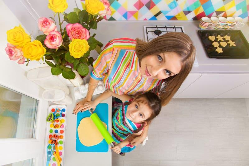 有她的准备在厨房的母亲的小女孩一个曲奇饼 免版税库存图片