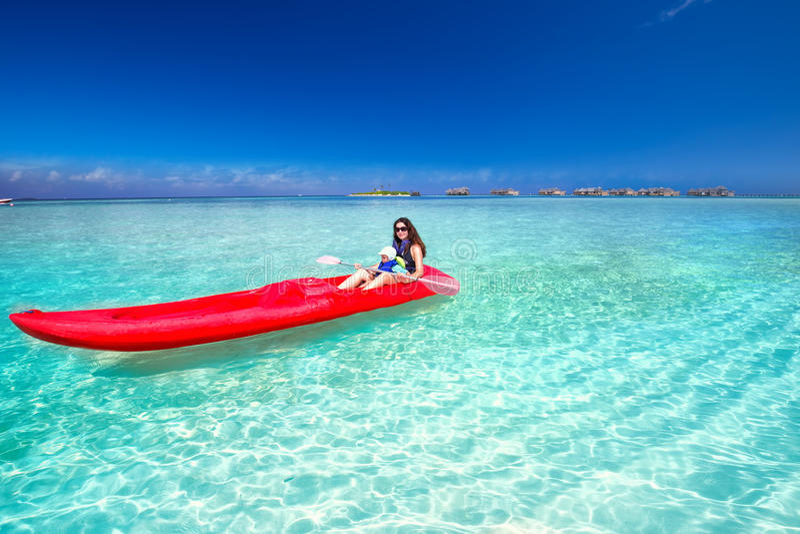 有她的划皮船在热带海岛上的小儿子的年轻白种人可爱的妇女 库存照片